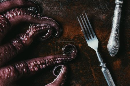 top view of big octopus with fork and knife on rusty metal surface