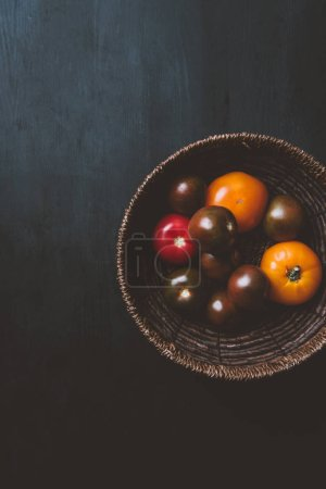 top view of yellow and red tomatoes in wicker bowl with copy space