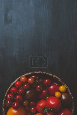 top view of red cherry tomatoes in wicker bowl on wooden background with copy space