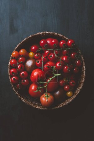 top view of red cherry tomatoes in wicker bowl