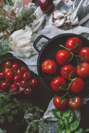 Photo for Top view of different red tomatoes in frying pan on gauze with flowers, onion, garlic and basil - Royalty Free Image