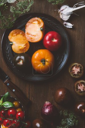 top view of different tomatoes on ceramic plate with knife on wooden background