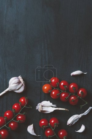 top view of red cherry tomatoes and garlic on black wooden background with copy space