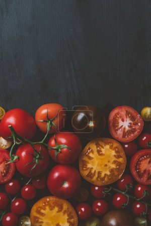 top view of different red and yellow tomatoes on wooden background with copy space