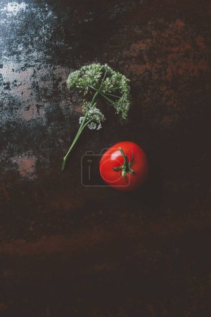 top view of red tomato and parsley flower on rusty background