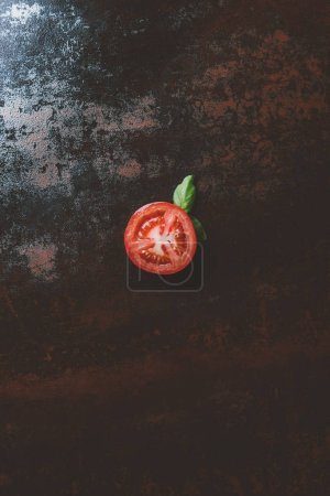 top view of half of red ripe tomato with basil leaves on rusty background