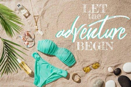 Photo pour Vue de dessus de bikini bleu avec divers accessoires et galets sur la plage de sable avec inspection «que l'aventure commence» - image libre de droit