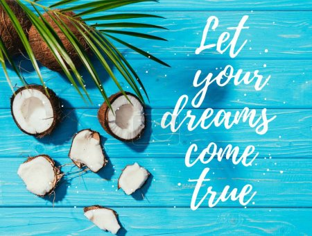 "top view of coconuts and green palm leaves on turquoise wooden surface with ""let your dreams come true"" lettering"