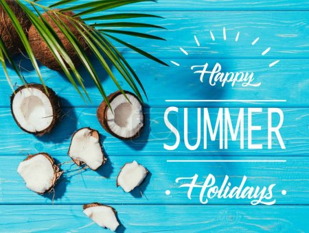 "top view of coconuts and green palm leaves on turquoise wooden surface with ""happy summer holidays"" lettering"