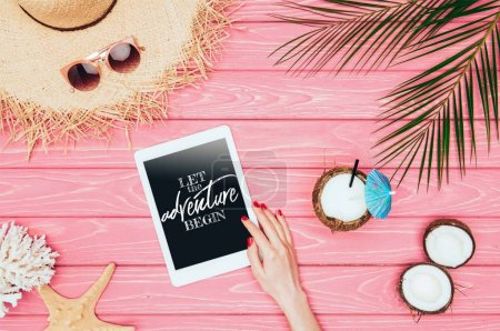 """cropped shot of woman using tablet with """"let the adventure begin"""" lettering on pink wooden surface with coconut cocktail and straw hat"""