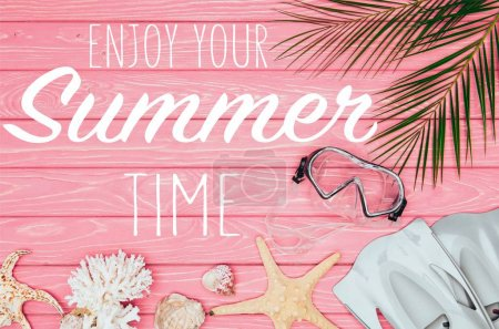 """top view of diving mask with flippers on pink wooden surface with """"enjoy your summer time"""" lettering"""