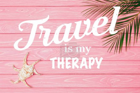 "top view of seashell with palm leaves on pink wooden surface with ""travel is my therapy"" lettering"