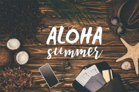 "Photo for Top view smartphone and flight tickets surrounded with various tropical travel attributes on wooden surface with ""Aloha summer"" lettering - Royalty Free Image"