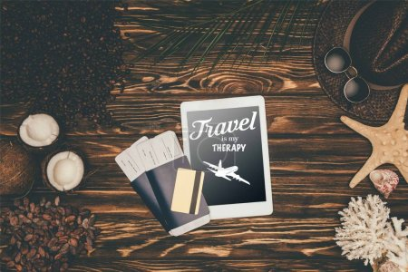 "top view of digital tablet and flight tickets surrounded with various tropical travel attributes on wooden surface with ""travel is my therapy"" lettering"