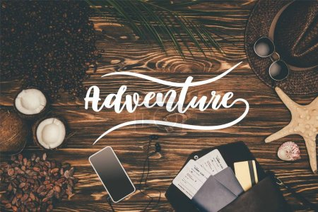 "Photo for Top view smartphone and flight tickets surrounded with various tropical travel attributes on wooden surface with ""adventure"" lettering - Royalty Free Image"