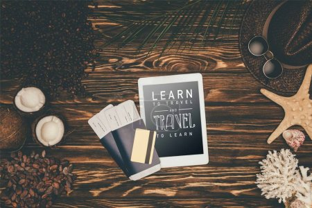 "top view of digital tablet and flight tickets surrounded with various tropical travel attributes on wooden surface with ""learn to travel and travel to learn"" lettering"