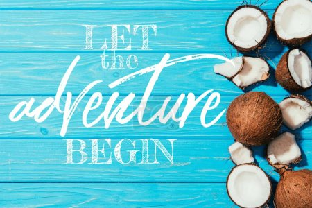"top view of whole coconuts and pieces on turquoise wooden surface with ""let the adventure begin"" inspection"