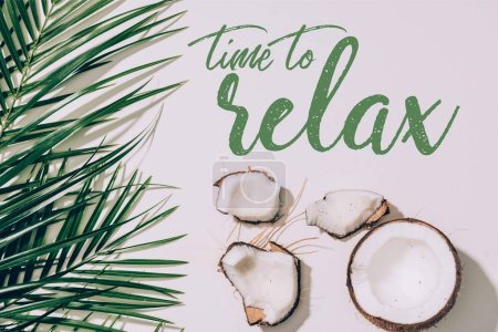 "pieces of organic healthy coconut and green palm leaves on white with ""time to relax"" inspection"