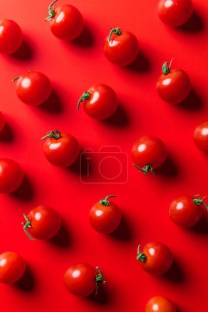 top view of pattern of cherry tomatoes on red surface