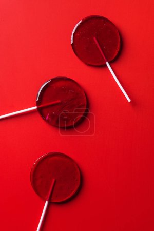 top view of three lollipops on red surface