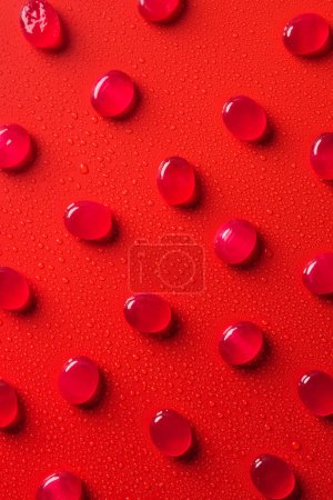 top view of collection of candies on red surface with water drops
