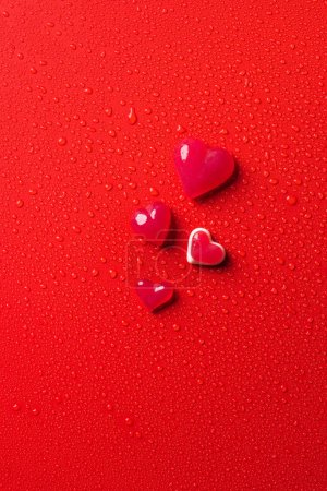Photo for Top view of heart shaped candies on red surface with water drops - Royalty Free Image