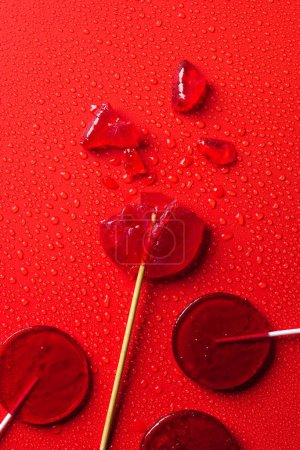 top view of lollipops on red surface with water drops