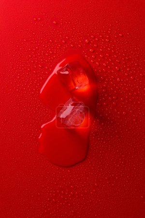 top view of melting ice cubes on red surface with water drops
