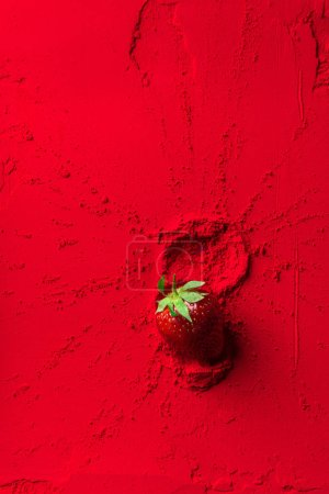 top view of red strawberry on red powder