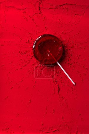 top view of red lollipop on red powder