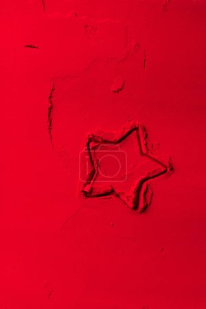 Photo for Elevated view of shape of cookie cutter in shape of star on red powder - Royalty Free Image