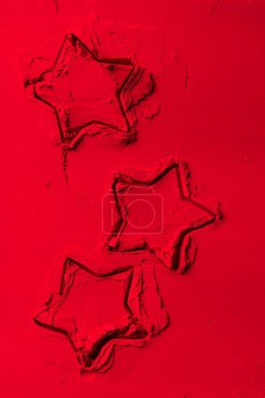 elevated view of shapes of cookie cutters in shape of stars on red powder
