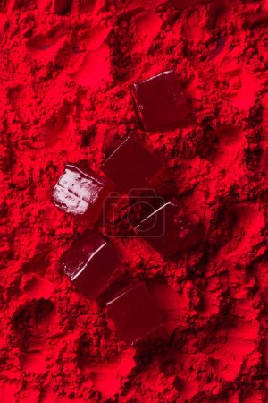 top view of scattered candies on red powder