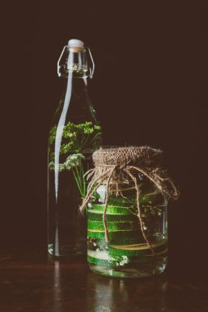 glass bottle with water and dill and glass jar with zucchini on wooden table on black