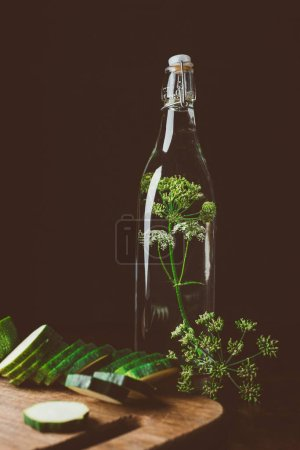 glass bottle with water and dill, cut zucchini on wooden board