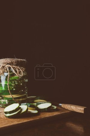 preserved zucchini in glass jar and cut zucchini on wooden board in kitchen
