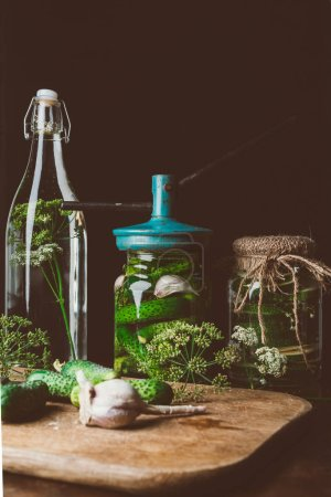 glass jars with preserved cucumbers and dill with garlic on table
