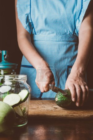 cropped image of woman cutting zucchini on wooden board at kitchen