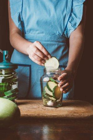 cropped image of woman adding zucchini into glass jar at kitchen
