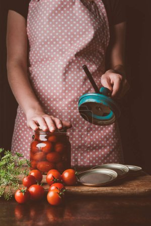 Photo for Cropped image of woman preparing preserved tomatoes at kitchen - Royalty Free Image