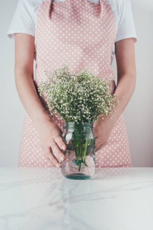 cropped image of woman holding jar with white flowers at kitchen