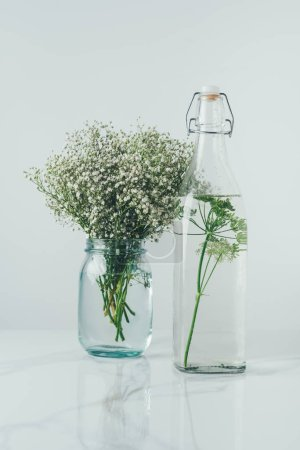 Photo for Glass bottle with water and dill and glass jar with flowers on white table - Royalty Free Image
