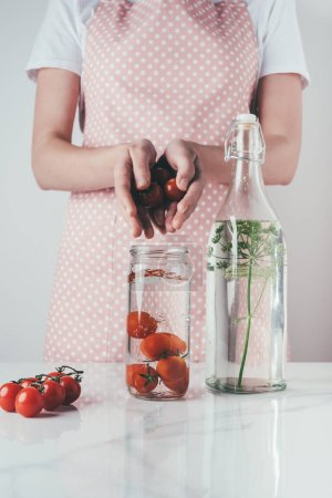 cropped image of woman putting tomatoes in glass jar with water at kitchen