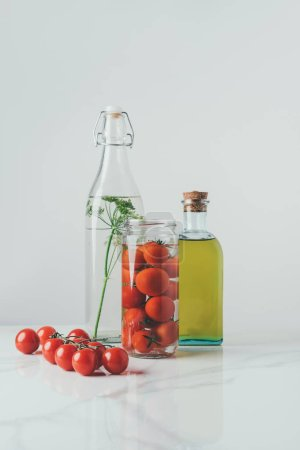 Photo for Glass jar with tomatoes, glass bottle with dill and bottle of oil on table - Royalty Free Image