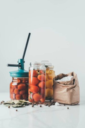 glass jars and tool for preserving tomatoes on table in kitchen