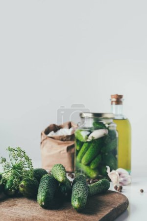 fresh cucumbers on cutting board on table with preserved cucumbers in glass jar on background