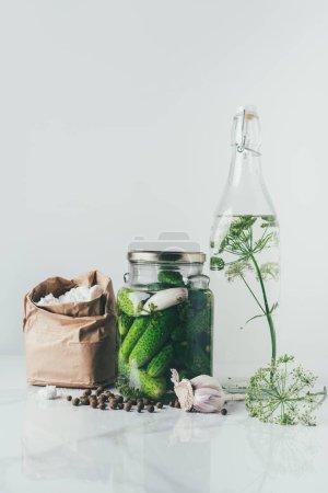 Photo pour Bocal en verre avec concombres conservés, bouteille en verre avec aneth et sel sur la table - image libre de droit