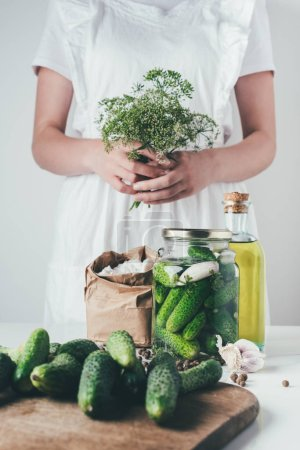 Photo for Cropped image of woman preparing preserved cucumbers and holding dill at kitchen - Royalty Free Image