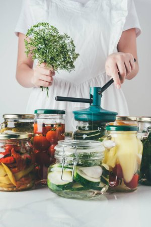 cropped image of woman preparing preserved vegetables in glass jars at kitchen