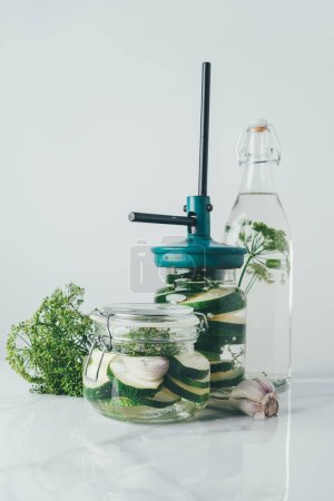 glass jars and bottle with zucchini and dill for preserving on kitchen table